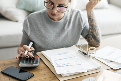woman with glasses and tattoos looking at papers with a calculator